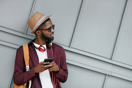 Foto de Handsome Black Man In Fashion Clothes With Phone On Street. Stylish African Man WIth Headphones And Phone In City. High Resolution - Imagen libre de derechos