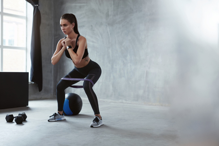 Photo for Squats. Sports Woman In Fashion Clothes Squatting With Resistance Band, Exercising Home. High Resolution - Royalty Free Image