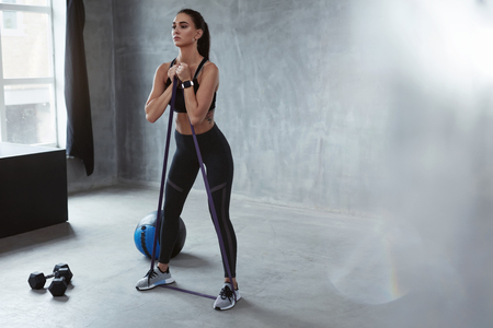Photo for Fitness Exercise. Sports Woman Exercising With  Resistance Band In Fashion Clothes, Loop Workout. High Resolution - Royalty Free Image