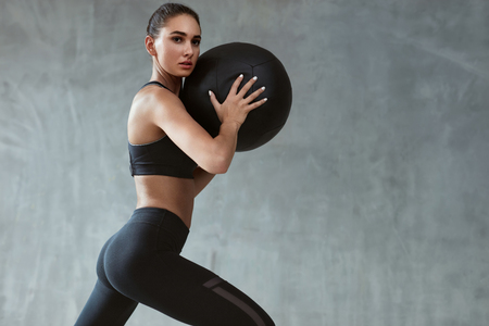 Sports Woman Training In Fashion Black Sportswear, Workout With Fitness Ball On Grey Background. High Resolution