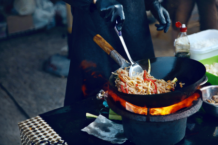 Foto de Cooking Food On Fire On Street Festival. Chef Cooking Thai Dish In Wok Outdoors. High Resolution - Imagen libre de derechos