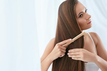 Photo pour Hair Care. Woman Combing Beautiful Long Hair With Wooden Brush - image libre de droit