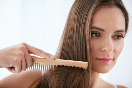 Photo pour Hair Care. Woman Combing Beautiful Healthy Long Hair With Wooden Brush. High Resolution - image libre de droit