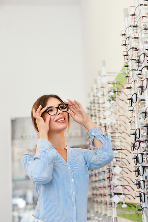 Photo pour Eyeglasses Store. Woman Choosing Glasses For Eyesight Correction, Trying On Eyewear. High Resolution - image libre de droit