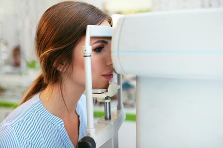 Photo pour Eyesight Exam. Woman Checking Eye Vision On Optometry Equipment, Eye Care Center. High Resolution - image libre de droit