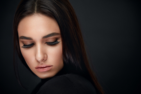 Photo pour Eyelashes Makeup. Woman Beauty Face With Long Black Lashes Extensions And Beautiful Makeup On Black. High Resolution - image libre de droit