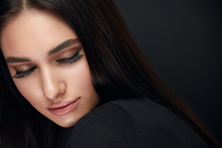 Foto de Eyelashes Makeup. Woman Beauty Face With Long Black Lashes Extensions And Beautiful Makeup On Black. High Resolution - Imagen libre de derechos