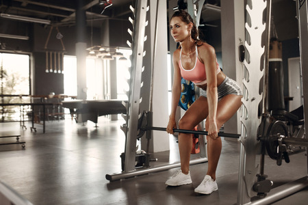 Photo for Workout. Athlete woman exercising, doing deadlift exercise in machine at gym. Female in sportswear training at fitness club - Royalty Free Image