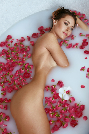 Foto de Spa. Woman in bath with milk and flowers enjoying body skin treatment. Girl with sexy naked body lying in bath tub with white water and red petals - Imagen libre de derechos