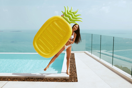 Photo pour Summer fun. Happy girl near infinity swimming pool with pineapple float enjoying vacation. Smiling woman with pool toy outdoors on sunny day - image libre de droit