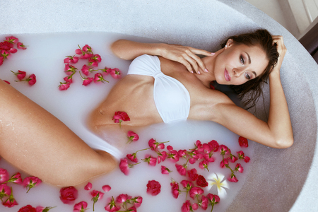 Foto de Body skin care. Woman at spa relaxing in bath with milk and flowers. Girl in white swimsuit enjoying spa treatment, lying in bath tub with white water and red petals - Imagen libre de derechos