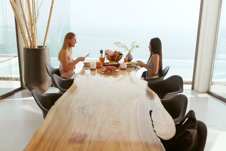 Photo pour Women eating breakfast at dinning room at luxury hotel outdoors. Female friends sitting at table, enjoying morning meal at resort with sea on background. - image libre de droit