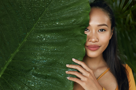 Photo pour Skin care. Woman model with beauty face and natural green leaf plant. Portrait of beautiful asian girl with nude nails and sexy smile in tropical nature - image libre de droit