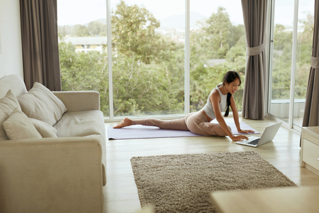 Foto de Girl doing yoga training at home while using computer. Beautiful asian woman practicing pigeon pose, stretching body on yoga mat and watching tutorial on laptop in living room - Imagen libre de derechos