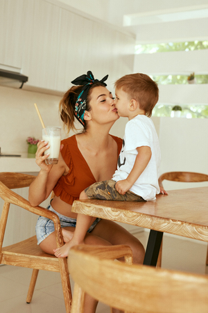 Photo for Mother kissing her child at table in kitchen in morning. Woman kisses boy while having a glass of healthy vegan milk for breakfast - Royalty Free Image