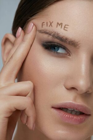 Beauty makeup. Woman face with messy eyebrow and fix me sign on skin closeup. Girl model with bushy fluffy messed up eyebrows and words written above. Eyebrow correction concept