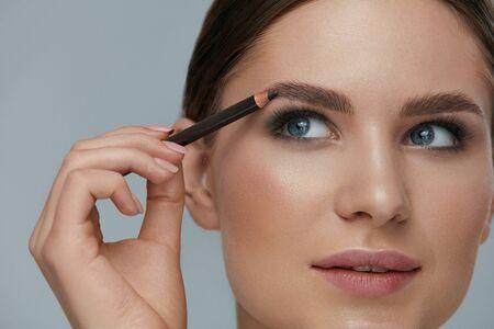 Foto de Beauty makeup. Woman shaping eyebrow with brow pencil closeup. Girl model with professional makeup contouring eyebrows - Imagen libre de derechos