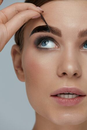 Photo pour Eyebrow cosmetics. Woman taking off brow gel tint from eyebrow closeup. Girl model peeling off peel-off eyebrow beauty product - image libre de droit