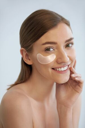 Photo pour Eye skin beauty. Happy woman with transparent under eye patch, beauty mask on face portrait. Smiling girl using translucent collagen pad on white background - image libre de droit