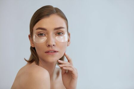 Photo pour Eye skin care. Woman with beauty patch mask under eyes portrait. Girl using eye patches, transparent collagen pads on light background - image libre de droit