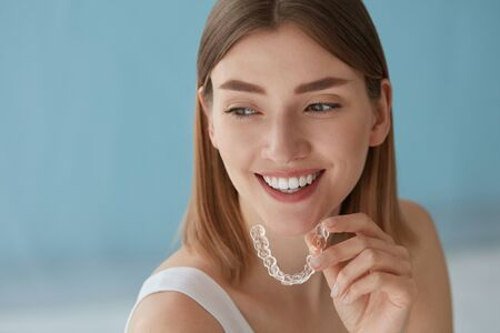 Foto de Teeth whitening. Woman with white smile, healthy straight teeth using clear removable braces, invisible teeth tray. Portrait of girl doing dental beauty treatment - Imagen libre de derechos