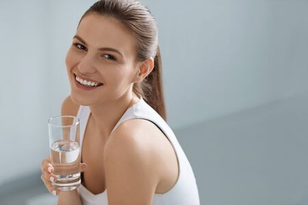 Photo pour Drink water. Smiling woman holding fresh pure water in glass portrait indoors - image libre de droit
