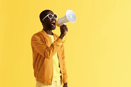 Foto de Advertising. Man screaming announcement in megaphone on yellow background. Portrait of african american male model in fashion wear using loud speaker in studio - Imagen libre de derechos