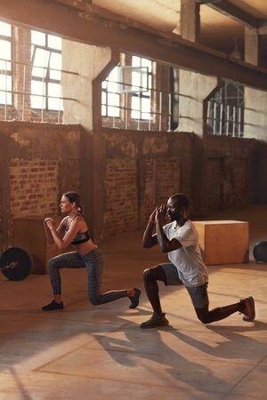 Photo for Sport couple doing leg lunge exercise workout at gym. Fit athlete people in sports clothes exercising lunges having fitness training indoors - Royalty Free Image