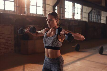 Foto de Sport woman doing fitness exercise with dumbbells at gym. - Imagen libre de derechos