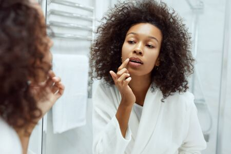 Photo pour Lips skin care. Woman applying lip balm looking in mirror at bathroom. Portrait of beautiful african girl model with beauty face and natural makeup applying lip product with finger - image libre de droit