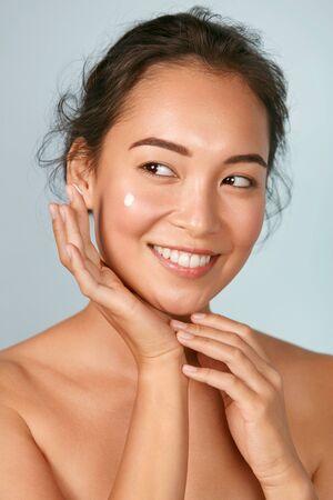 Photo pour Face skin care. Woman applying cosmetic cream on skin portrait - image libre de droit