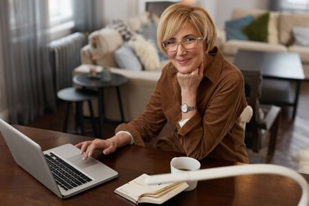 Photo for Businesswoman. Female Uses Laptop. Mature Woman Remote Homework Concept. Older Model in Brown Jacket And Eyeglasses Uses Notebook. - Royalty Free Image