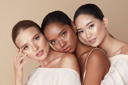 Photo pour Beauty. Group Of Diversity Models Portrait. Multi-Ethnic Women With Different Skin Types Posing On Beige Background. Tender Multicultural Girls Standing Together And Looking At Camera. - image libre de droit