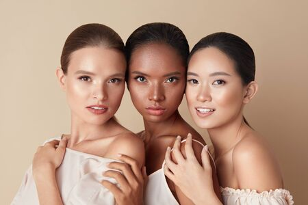 Foto de Beauty. Portrait Of Diversity Models. Mixed Race, Asian And Caucasian Girls Hugs Each Other And Looking At Camera. Different Ethnicity Women With Nude Makeup And Perfect Glowing Skin. - Imagen libre de derechos