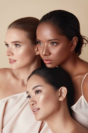 Photo pour Diversity. Women Beauty Portrait. Multi-Ethnic Models Standing Together And Looking Away. Asian, Mixed Race And Caucasian Female With Natural Makeup And Healthy Skin On Beige Background. - image libre de droit