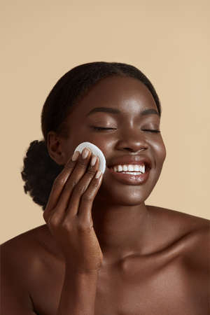 Photo pour Portrait close up of beautiful black girl touch her clean face with cotton pad. Smiling young woman with closed eyes. Concept of face skin care. Isolated on beige background. Studio shoot - image libre de droit
