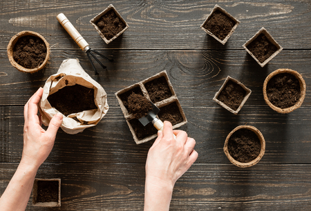 Photo pour Woman pours ground in the eco friendly pots to plant seedlings,pots on wooden background, small bag with ground and garden trowel and rakes - image libre de droit