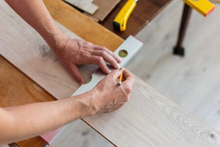 Photo pour Installation laminate or parquet in the room, worker installing wooden laminate flooring, marking the length of the laminate - image libre de droit