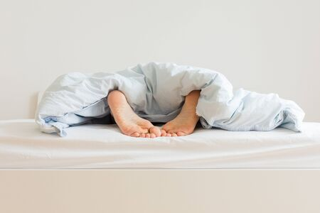 Photo pour Part of the home or hotel interior, male legs peek out from under the covers, man sleeping on a white bed with blue linens in the morning - image libre de droit
