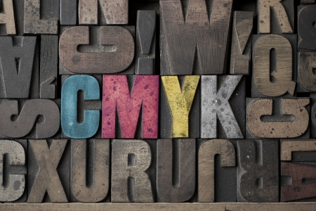 The Letters CMYK written out in very old and worn letterpress type