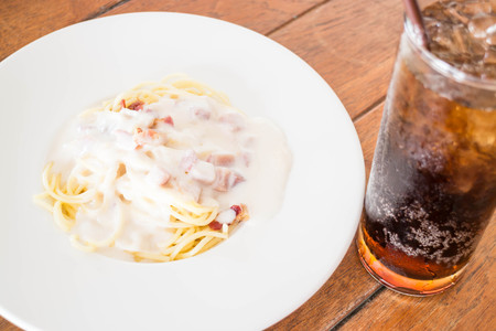 Spaghetti carbonara with ham cheese and cola, stock photo