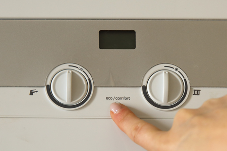 Photo for Woman hand push an installation button of home gas heating boiler close up - Royalty Free Image
