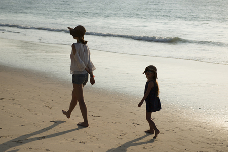 Mother and daughter walking on sandy beach at sunsetの写真素材