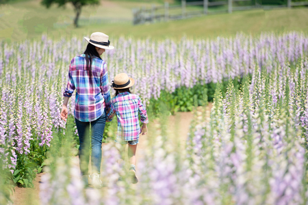 Photo pour Mother and daughter playing in the flower field - image libre de droit