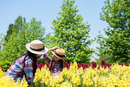 Foto de Mother and daughter playing in the flower field - Imagen libre de derechos