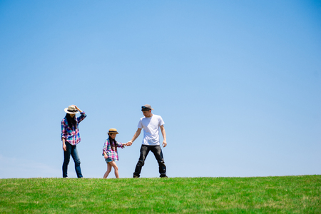 Photo for Father and mother and daughter playing in the meadow - Royalty Free Image