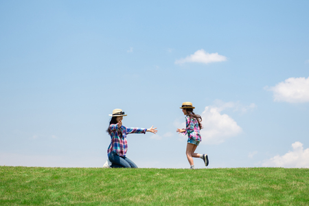 Photo pour Mother and daughter playing in the meadow - image libre de droit
