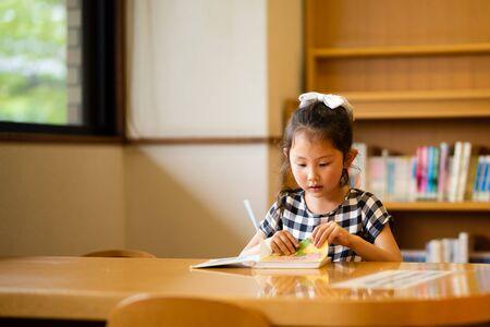 Foto de Girl reading a book in the library - Imagen libre de derechos