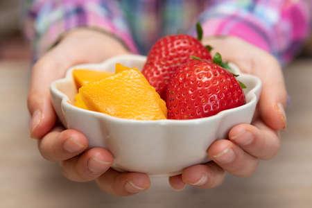 Photo pour Child's hand holding a bowl of fruit - image libre de droit