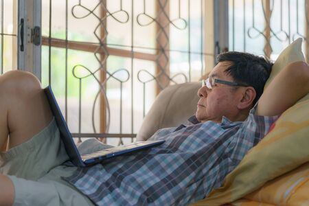 An elderly man falls asleep while using a laptop